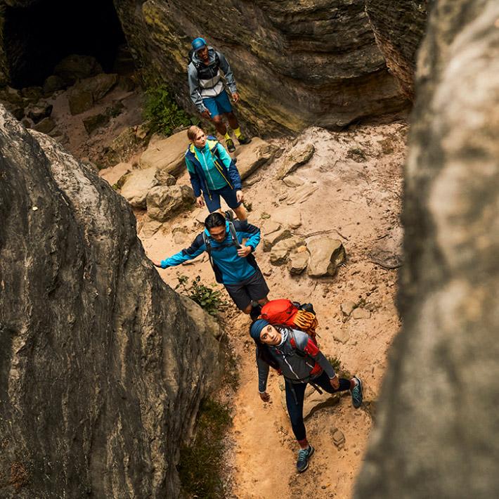 Vier Wanderer laufen zwischen Felsen
