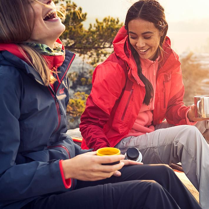 Zwei Frauen trinken aus Thermosbecher